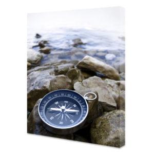 Obraz na płótnie pionowy kompas na skalistym nadbrzeżu